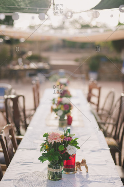 Centerpieces in a row on table at an outdoor wedding