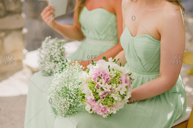 Bridesmaids holding flowers and wearing mint green dresses