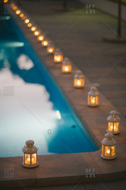 Illuminated lanterns lining a pool at night