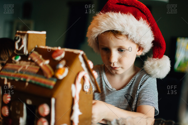 Boy decorating gingerbread house