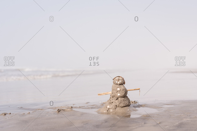 Snowman figure built from sand on a beach