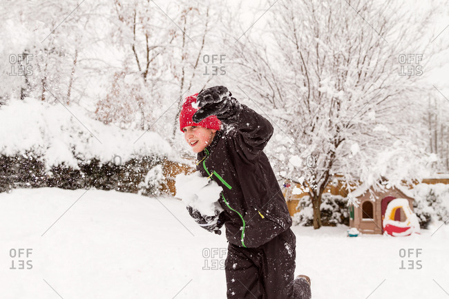 Child running with snowball