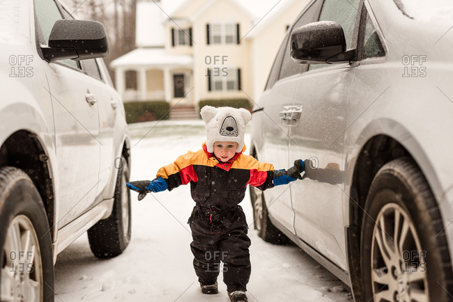 Toddler walking between two cars on snowy day