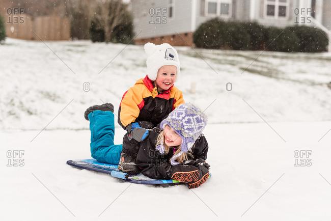 Two kids sledding together on a sled