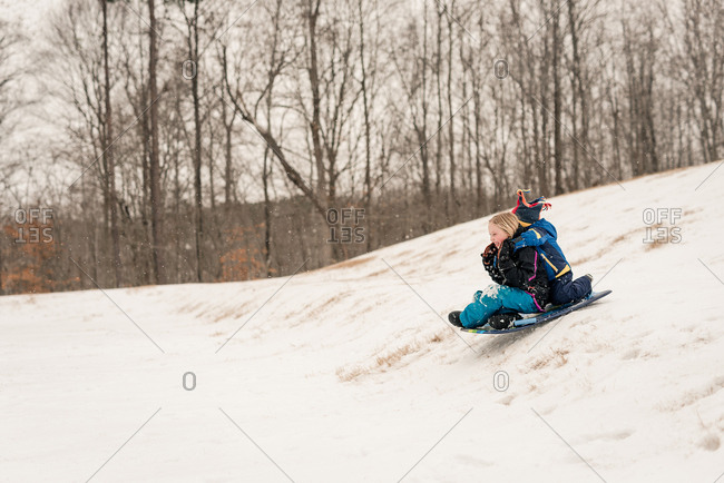 Two kids sledding down a hill on a sled