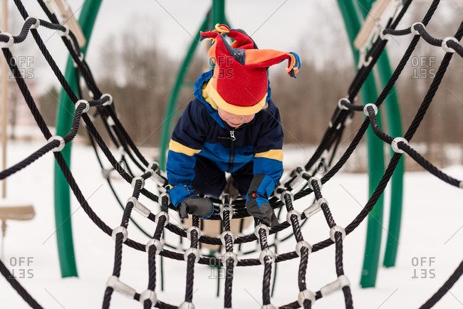 Boy climbing on rope at a playground during winter