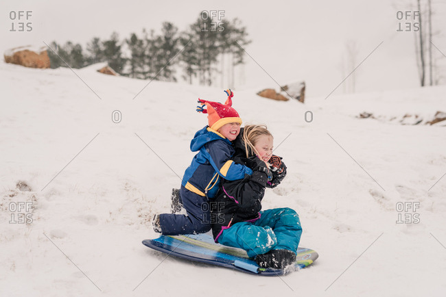 Siblings sledding down a hill on a sled