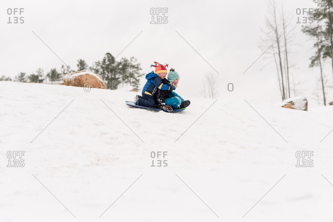 Brother and sister sledding down a hill on a sled