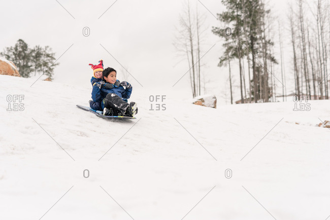 Brothers sledding down a hill on a sled