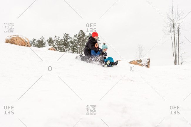 Three siblings sledding down a hill together on a sled
