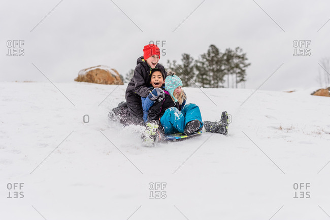 Three kids sledding down a hill together on a sled