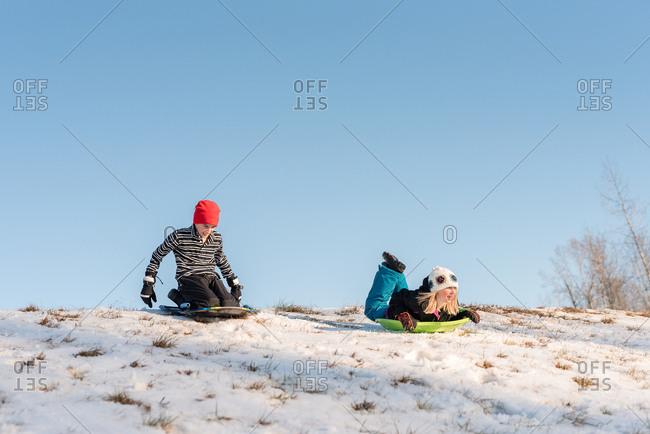 Kids sledding down a hill on sleds