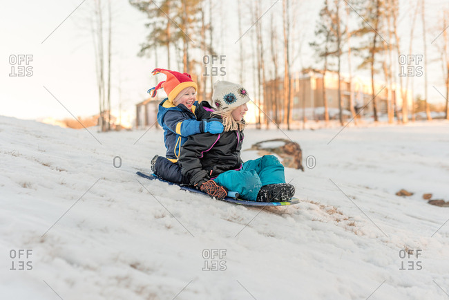 Happy kids sledding down a hill on a sled