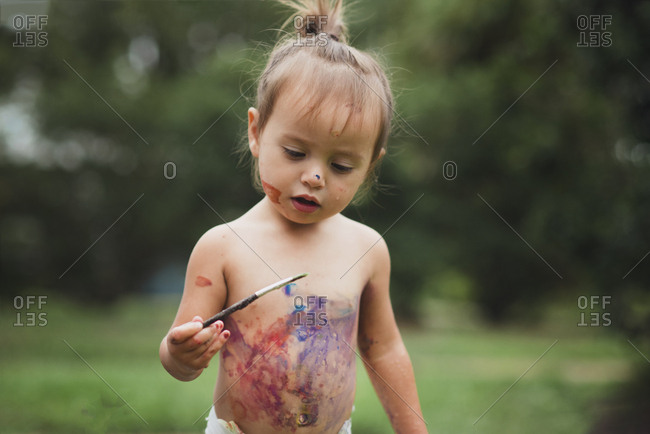 Toddler girl covered in paint