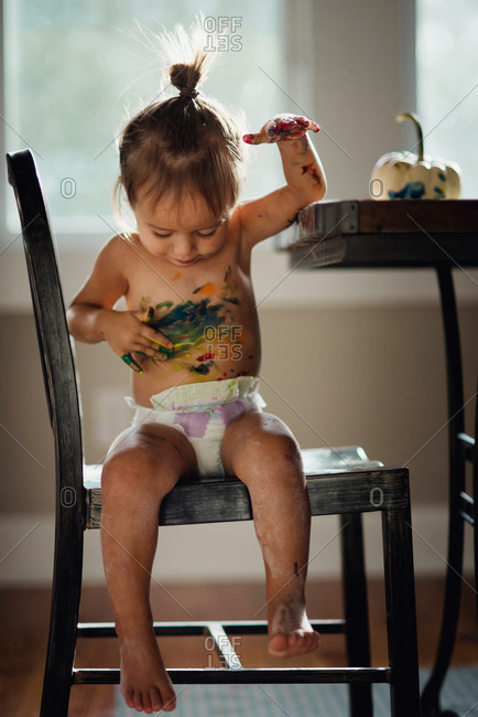 Toddler girl with paint all over her body