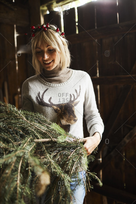 Blond woman, headdress, garland with rose hips, twigs of evergreens for decoration