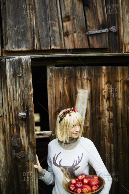 Blond woman, headdress, garland with rose hips, bowl with apples, barn door, half portrait,