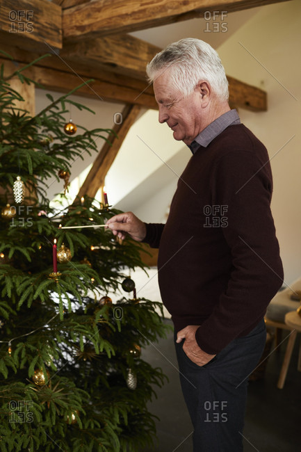 Grandfather decorating Christmas tree