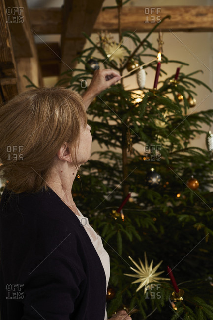Woman lights candles on Christmas tree, Christmas Eve