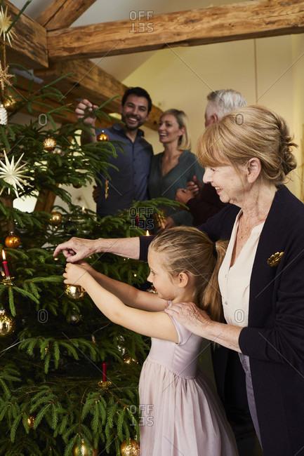Child with grandmother decorating Christmas tree, half portrait