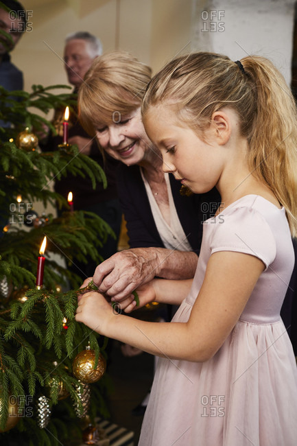Child with grandparents decorating Christmas tree, half portrait