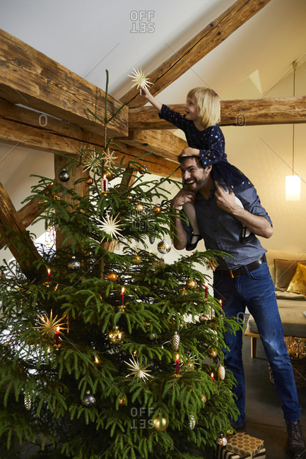 Man and child decorate the Christmas tree