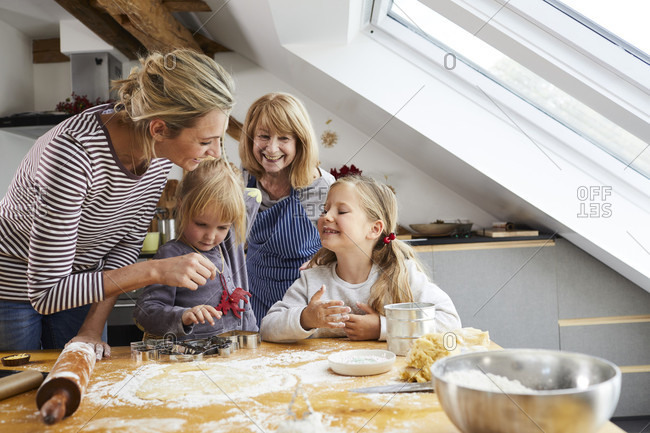 Grandmother, mother and daughters baking Christmas cookies,