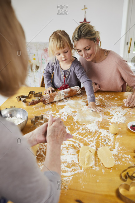 Grandmother, mother and little daughter baking Christmas cookies,