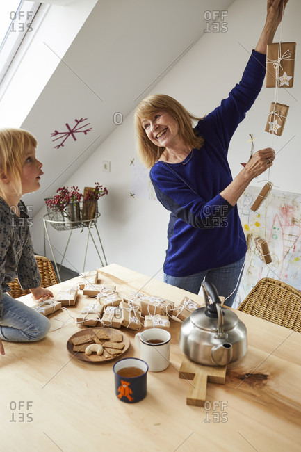 Grandmother and granddaughter cozy at home while crafting in Christmas time