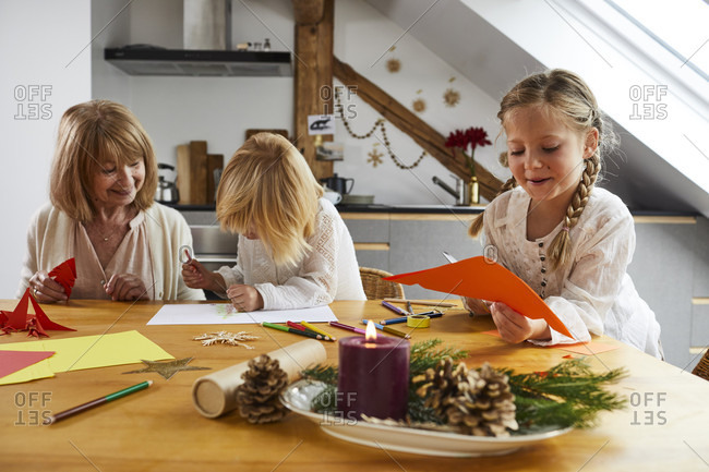 Grandmother and granddaughters while crafting at home in Christmas time