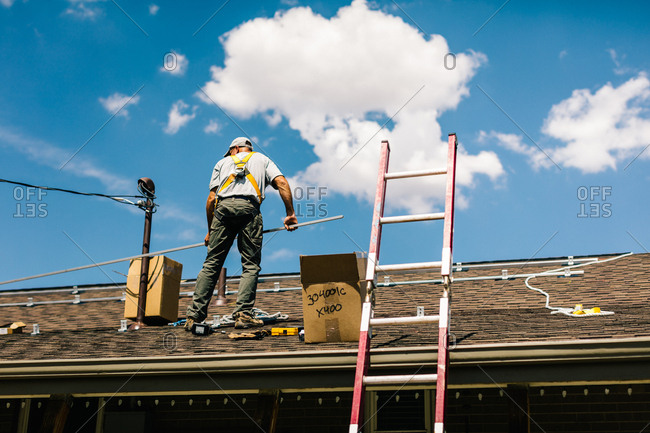 Low angle view of worker installing brackets for solar panels