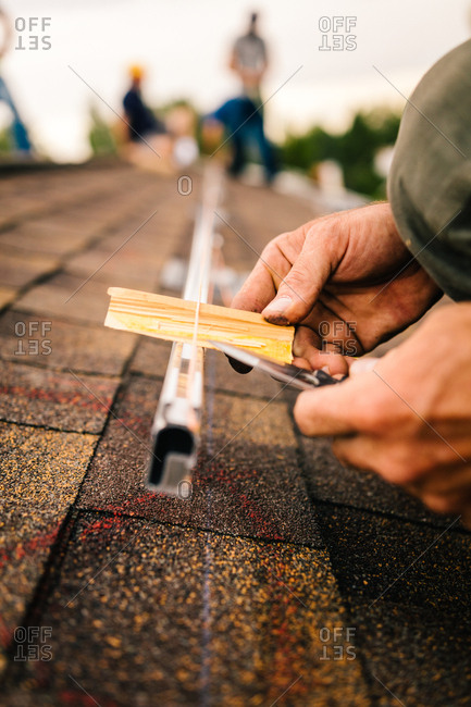 Men installing brackets for solar panels on a roof