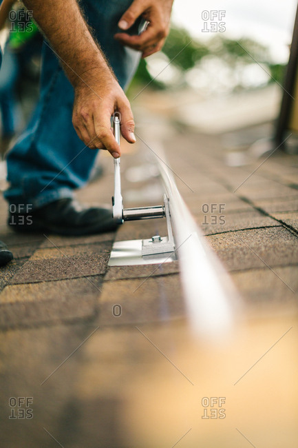 Man installing brackets for solar panels on a roof with a socket wrench