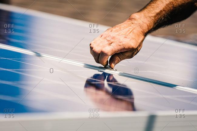 Man tightening nuts by hand on solar panels