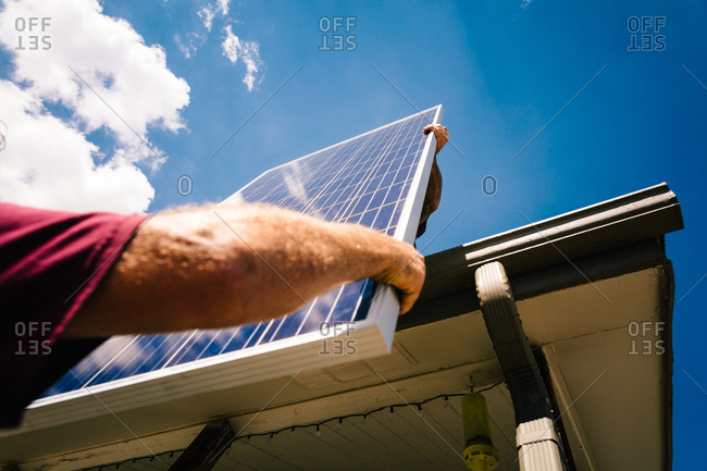 Men lifting solar panels onto a roof