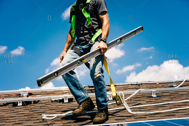Low angle view of construction worker holding a level on a roof