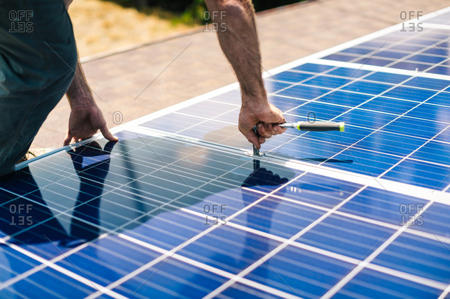 Man tightening nuts with a wrench on solar panels