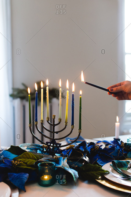 Person lighting menorah on table