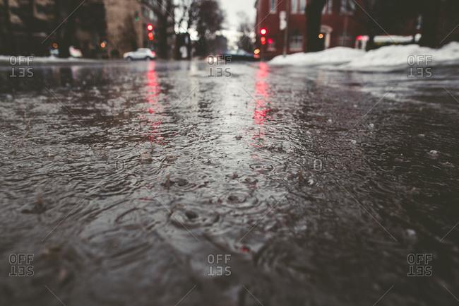 Rain water on city street in winter