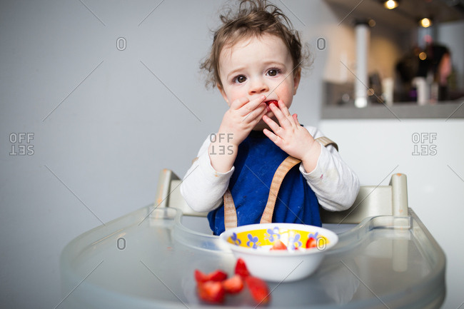 Toddler eating strawberries