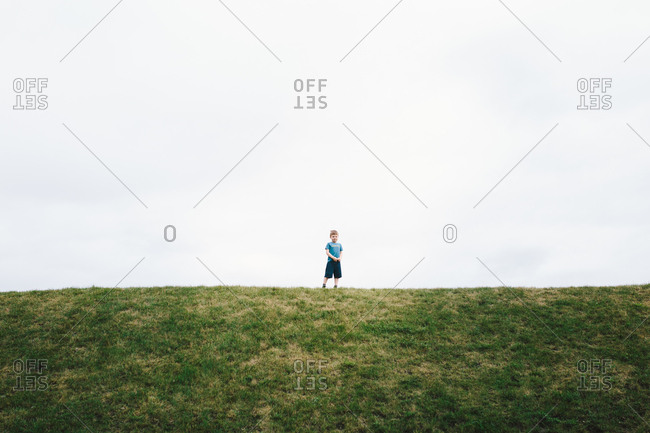 Boy standing on hill top