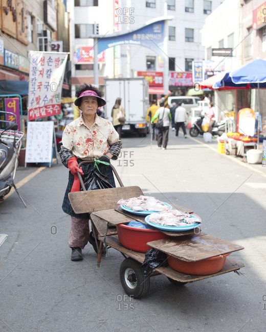 Busan, South Korea - May 4, 2012: A lady carting seafood to her stall, Jagalchi Fish Market, Busan, South Korea