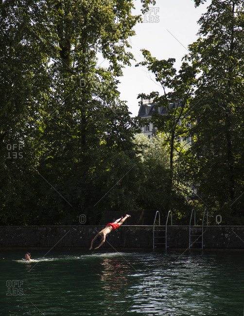 Zurich, Switzerland - June 7, 2014: Man diving into the Limmat River, Zurich, Switzerland