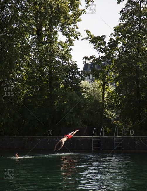 Zurich, Switzerland - June 7, 2014: Man diving into the Limmat River, Zurich, Switzerland