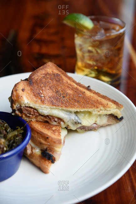 Grilled sandwich with cheese and meat served with a cocktail