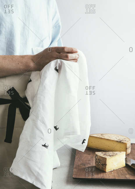 Chef standing in front of a fresh cut wheel of cheese