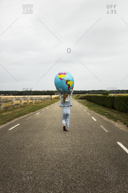 Girl walking on road holding globe