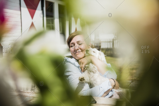 Woman cuddling with dog on terrace