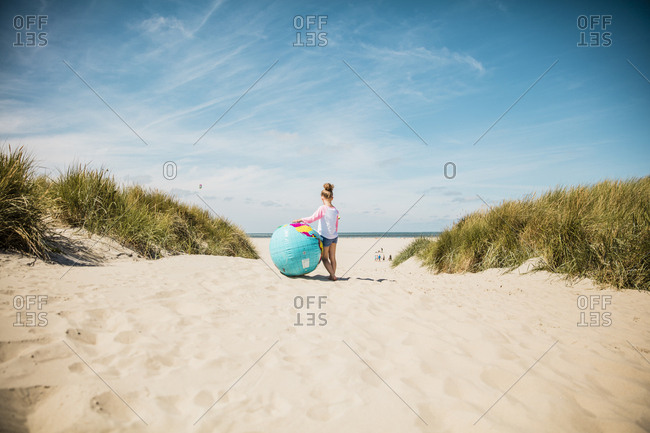 Girl with globe on the beach