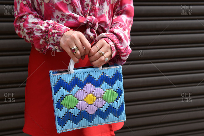 New York, NY - September 14, 2017: Woman in a colorful outfit holding a weaved leather handbag